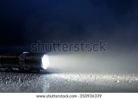 Tactical waterproof flashlight with water drops and fog - stock photo