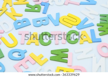 Tactical word with alphabet wood block backgroud - stock photo