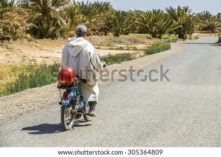 TAFILALT, MOROCCO, APRIL 12, 2015: Local man in traditional attire rides on motorbike in oasis