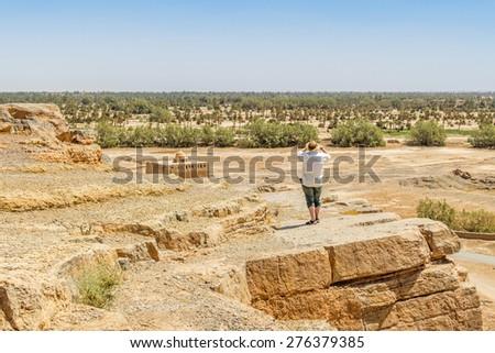 Tafilalt oasis in Morocco - senior tourist looks the landscape from Tinrheras ksar  - stock photo