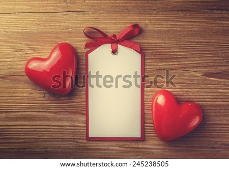 Tag and heart on the wooden background - stock photo