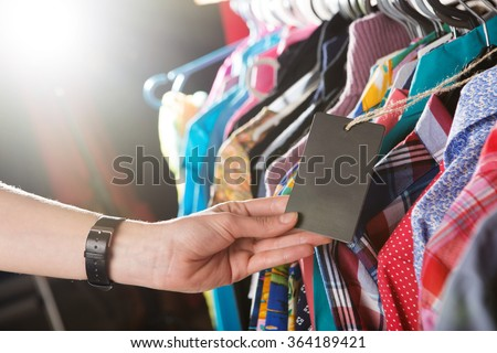 Tag in a hand - clothes hanging on the rack in the fashion store - stock photo