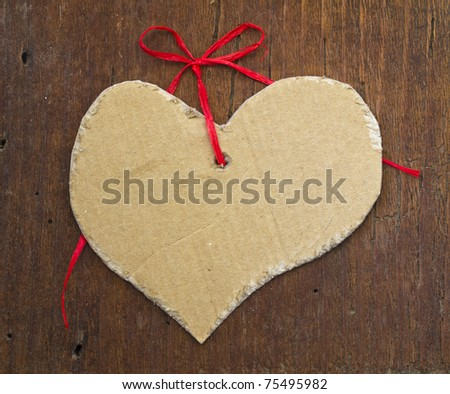 tag in the shape of heart on the wooden background - stock photo