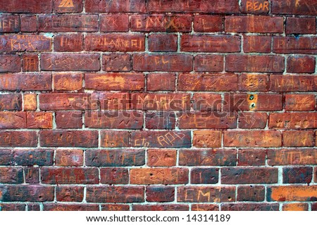 Tagged signatures of an urban brick wall. - stock photo