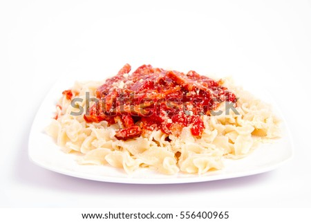 Tagliatelle mosse with tomato sauce with ham, sprinkled with parmesan