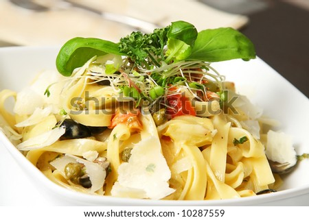 tagliatelle on table with salad and fork in background