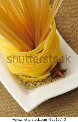 tagliatelle pasta and spaghetti with rosemary on white plate