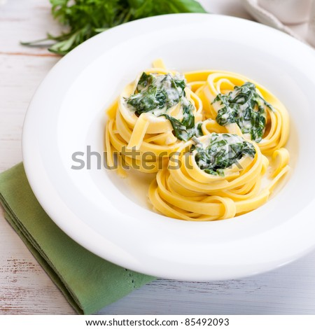 Tagliatelle pasta with blue cheese sauce and spinach - stock photo