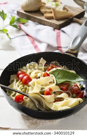 Tagliatelle Pasta with cherry tomatoes in a pan, on white wooden table and red checkered tablecloth