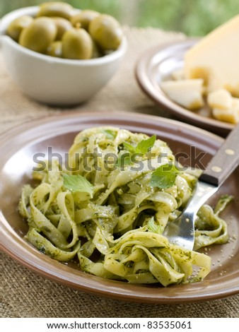 Tagliatelle pasta with pesto on brown plate. Selective focus - stock photo