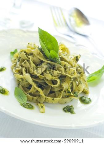 Tagliatelle pasta with pesto on white plate - stock photo