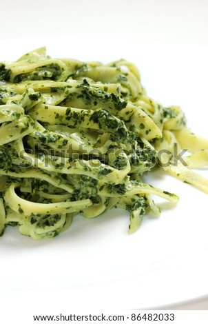 Tagliatelle pasta with spinach on white plate - stock photo