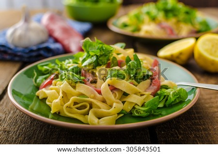 Tagliatelle with bacon, garlic and salad, homemade pasta from best italian flour - semolina - stock photo
