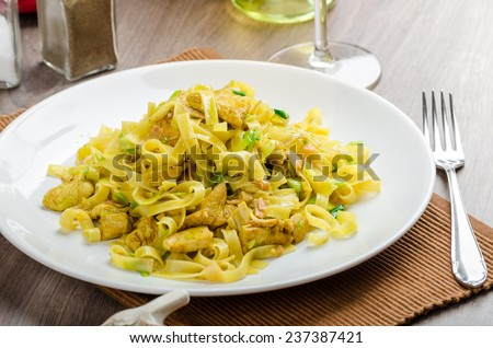 Tagliatelle with chicken curry, leek and garlic, home made, bio garlic, fresh vegetable and Italian white wine - stock photo