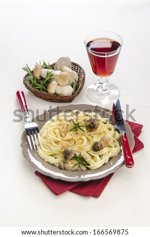 Tagliatelle with porcini mushrooms and rosemary with a wine glass in the background plpne - stock photo