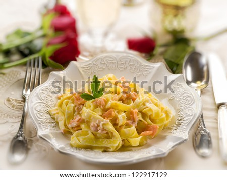 tagliatelle with salmon and cream sauce on luxury table, selective focus