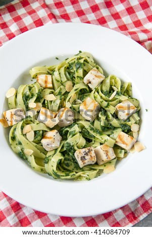 Tagliatelle with spinach and grilled salmon, fabric chequered, gray background, white plate.