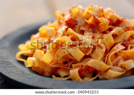 Tagliatelle with tomato sauce in wooden plate, close-up - stock photo