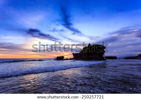Tahah Lot Temple and ocean waves at sunset, Bali, Indonesia - stock photo