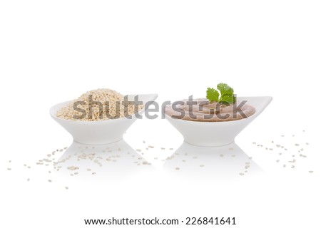 Tahini dip and sesame seeds in white bowls isolated on white background. African and middle eastern traditional cuisine.  - stock photo