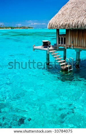 Tahiti Overwater Bungalow and turquoise water - stock photo