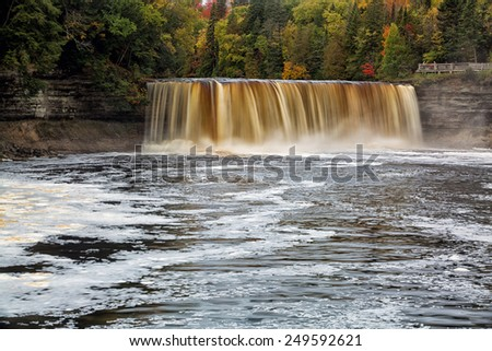Tahquemenon Falls in the Upper Peninsula of Michigan. Sometimes referred to as the root beer falls because of the tannin that leaches from the surrounding cedar forest and into the river water. - stock photo