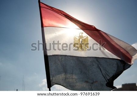 Tahrir square, Cairo, Egypt, January 2011, The Egyptian flag waving among the blue sky - stock photo