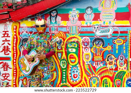 TAICHUNG, TAIWAN - circa MAY 2014: Street performer plays guitar in front of the colorful graffiti painted in the whole Rainbow village. It is a famous sightseeing spot in Taiwan.
