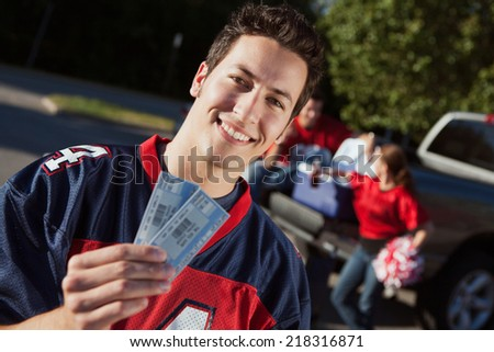Tailgate: Guy Fan Holds Up Football Game Tickets - stock photo