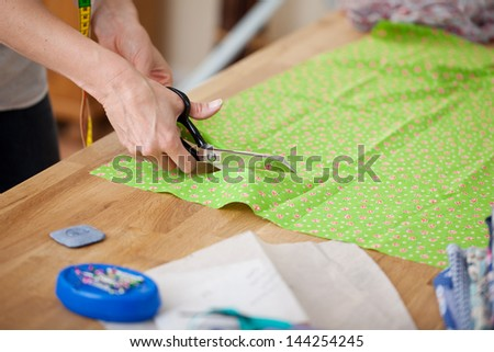 Tailor at work cutting fabric with scissors - stock photo