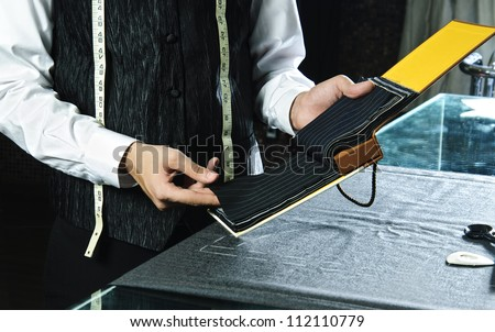 Tailor choosing suit textile from list of samples. - stock photo
