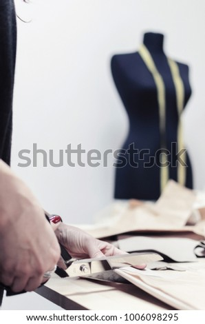 tailor cuts scissors, tailoring materials, closeup of professional female tailor using scissors and draft design cardboard on cloth material cut clothing design samples in production studio