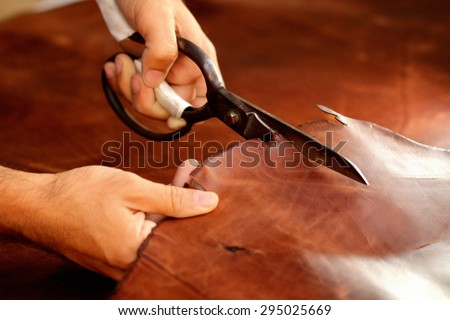 Tailor cutting animal skins, leather at textile factory / Old women's hands with cutting at textile factory - stock photo