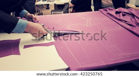 Tailor cutting fabric for bespoke suit - stock photo