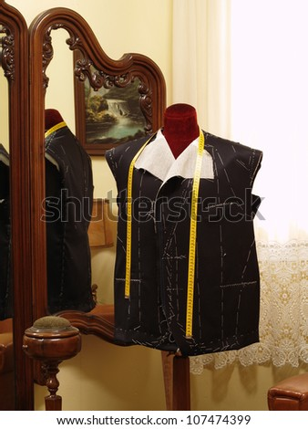 Tailor dummy with an unfinished coat. - stock photo
