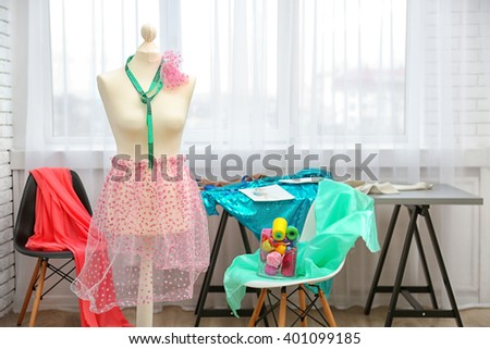 Tailor dummy with measuring tape in fashion studio - stock photo