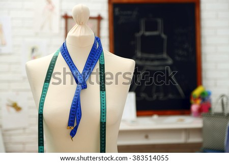 Tailor dummy with measuring tapes in fashion studio - stock photo