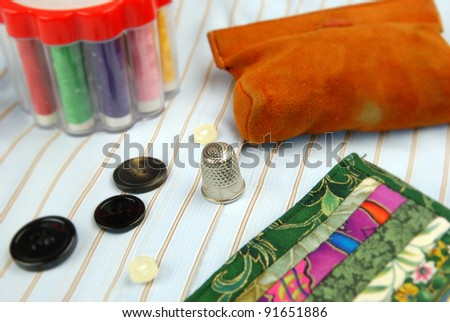 tailor equipment with finger hat thread and needle - stock photo