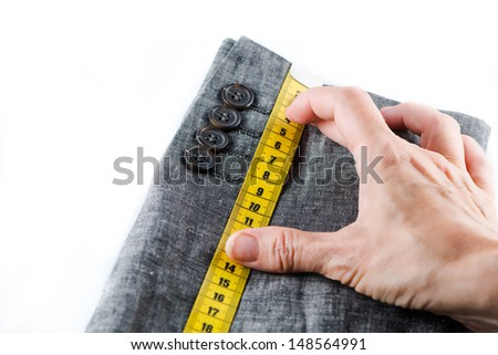 Tailor hand measuring with tape a man suit - stock photo