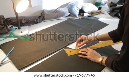 Tailor.Hands notch tailor tailor's scissors cloth. Female tailor stitching material at workplace. Preparing fabric for clothes making. Tailoring, garment industry, designer workshop concept.
