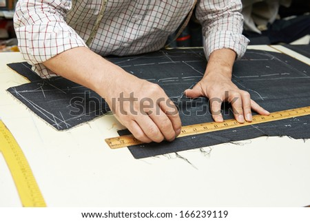 Tailor hands working with measure bar - stock photo