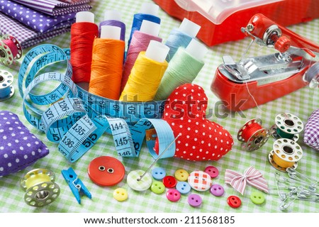 Tailor items: spools of colorful thread, buttons, fabrics, measuring tape, pincushion, small sewing mac�hine and measuring tape - stock photo