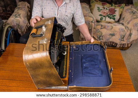 Tailor Man Keeping his Sewing Machine in a Vintage Case On top of a Wooden Table In the Living Room. - stock photo