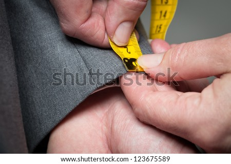 Tailor measuring the size for a tailor made suite for a male model - stock photo