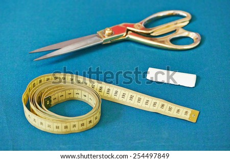 Tailor or sewing tools. Cloth, scissors, measure tape, chalk - stock photo
