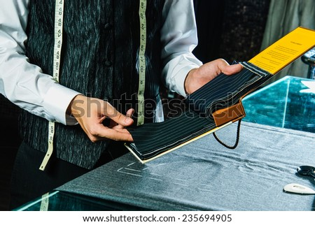 Tailor's hands chooses fabric. - stock photo