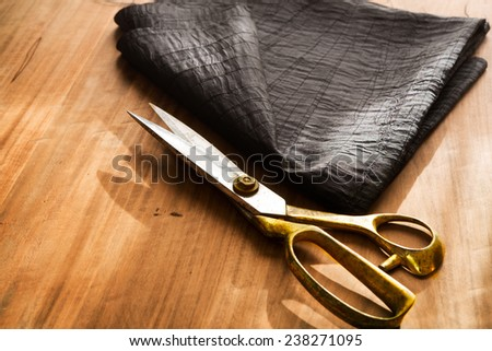 Tailor's work table. textile or fine cloth making.Gold scissors and black silky fabric.  - stock photo