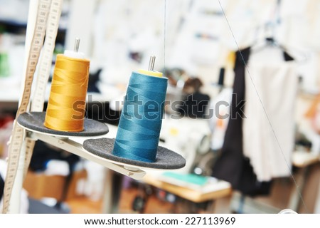 tailor sewing concept, reals of thread in workshop - stock photo