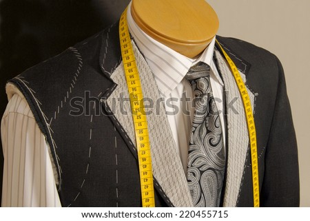 Tailor shop mannequin with measuring tape across neck. - stock photo