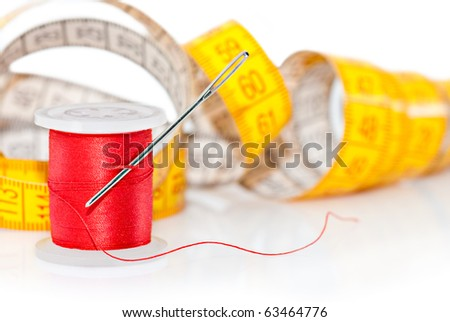 Tailor tools for craft. Bobbin for sewing, needle and measuring tape over white - stock photo